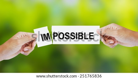 Businessman tearing the word Impossible for Possible - stock photo