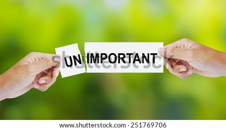 Businessman tearing the word Unimportant for Important - stock photo
