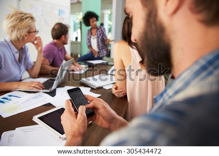 Businessman Texting During Meeting In Office