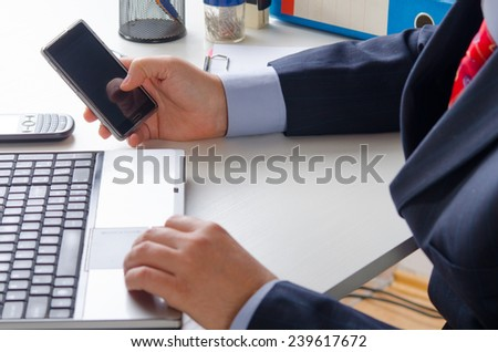Businessman texting on the smart phone in the office. - stock photo