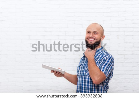 Businessman Think Holding Tablet Computer, Casual Bearded Business Man Look Up To Copy Space Office White Brick Wall - stock photo
