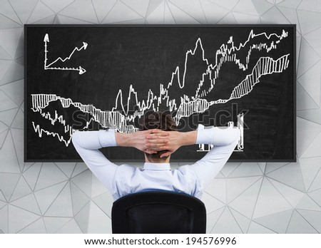 Businessman thinking about a chart on the blackboard  - stock photo