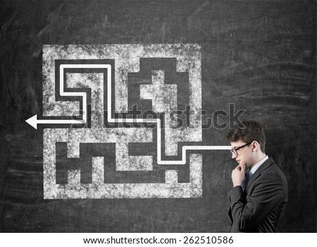 businessman thinking and drawing maze on blackboard - stock photo