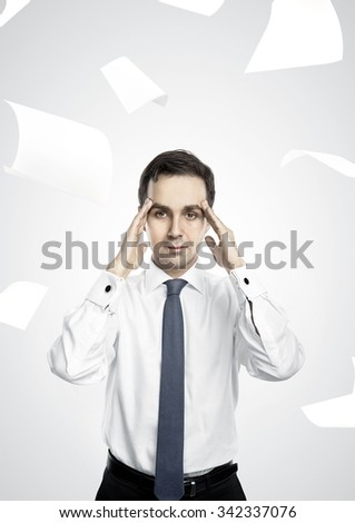 businessman thinking and falling paper over head - stock photo