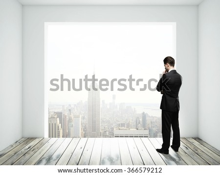 businessman thinking and looking in big window in room - stock photo