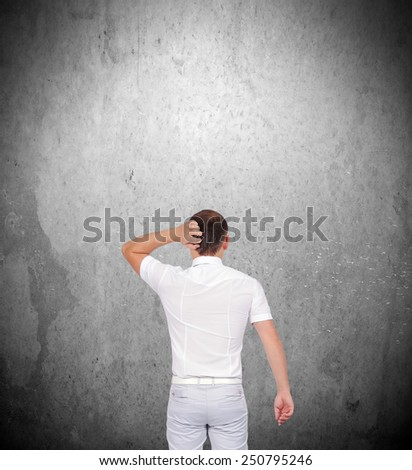 businessman thinking and looking on gray concrete wall - stock photo