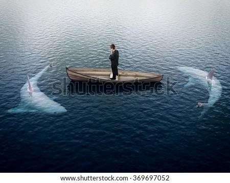 businessman thinking and sharks around him - stock photo