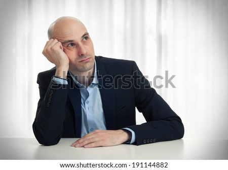 businessman thinking at his desk. Looking up - stock photo