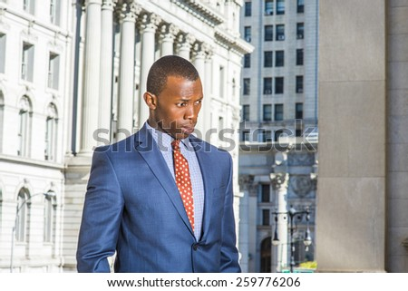 Businessman thinking hard. Dressing in blue suit, patterned tie, a young black guy standing in the front of vintage style office building, looking down, frowned, confused, sad, lost in thought.  - stock photo