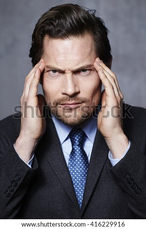 Businessman thinking hard in studio, portrait