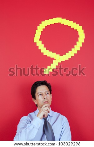 Businessman thinking next to a red wall - stock photo