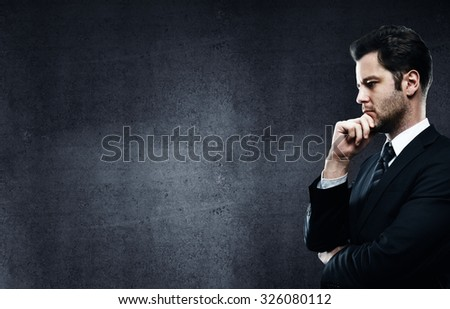 businessman thinking on a gray concrete wall background - stock photo