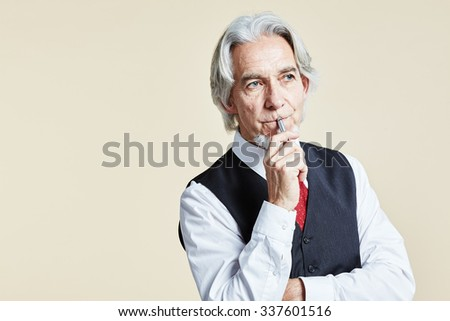 Businessman thinking with his pen at lips