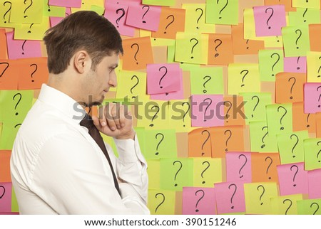 Businessman thinking with question marks written on adhesive notes stuck - stock photo