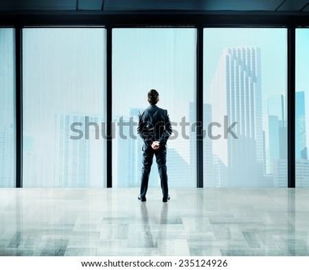 Businessman thinks about future from a skyscraper - stock photo