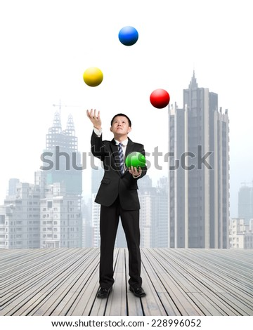 businessman throwing and catching colorful balls on wooden floor with cityscape background - stock photo