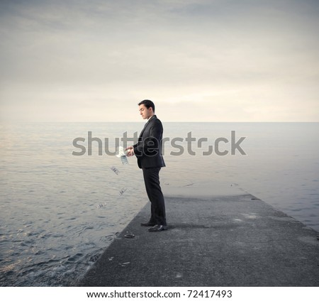 Businessman throwing some banknotes in the sea - stock photo