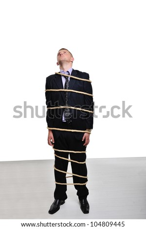 Businessman tied up with a rope looking up