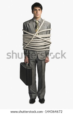 Businessman tied up with ropes and holding a briefcase - stock photo