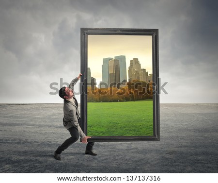 businessman tired carries large frame with landscape photos