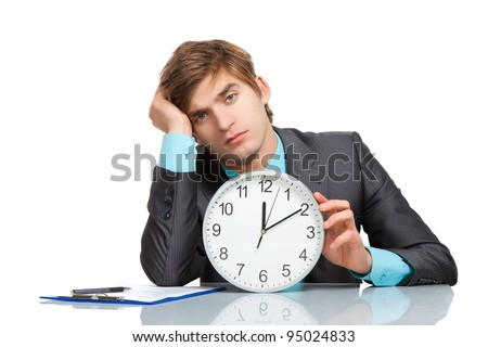Businessman tired hold clock, sitting at the desk, handsome young business man bored looking at camera, wear elegant suit and tie isolated over white background - stock photo