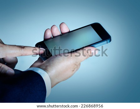 Businessman touch press mobile smart phone on blue background
