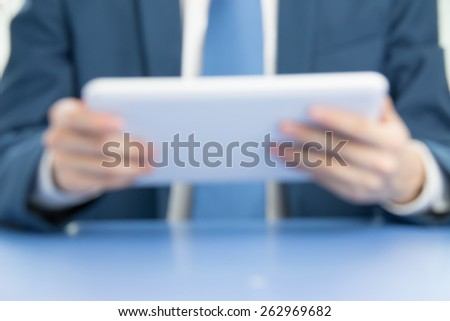businessman touch tablet to businessman in blur background - stock photo