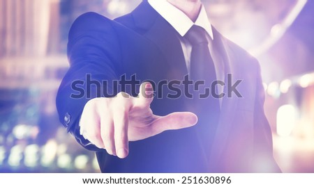 Businessman touching a touch screen on blurred city background - stock photo