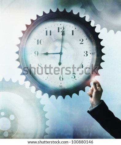 Businessman touching cog wheel with clock face in center