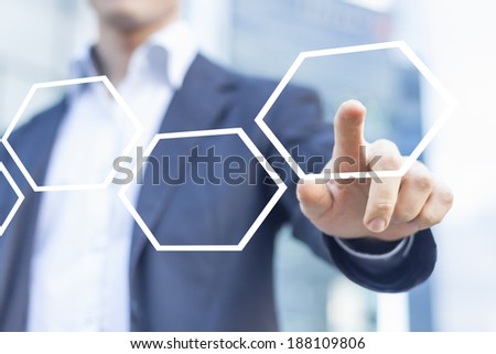 Businessman touching hexagonal button in workflow with honeycomb pattern - stock photo
