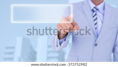 Businessman touching invisible screen against low angle view of city buildings - stock photo