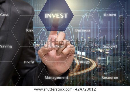 Businessman touching the Invest icon with business success virtual screen on Trading graph on the cityscape at night background, Business technology concept - stock photo