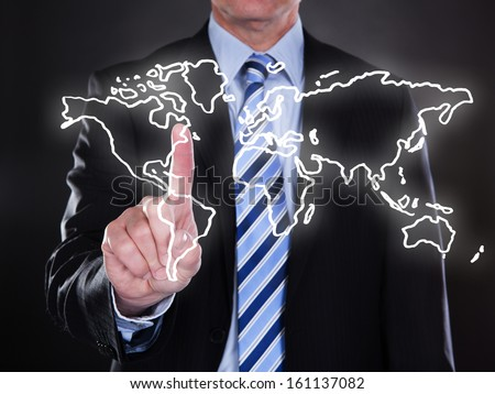 Businessman touching world map on the screen over black background