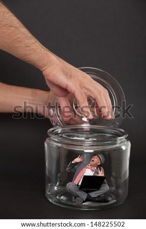 Businessman trapped inside a transparent glass jar  - stock photo