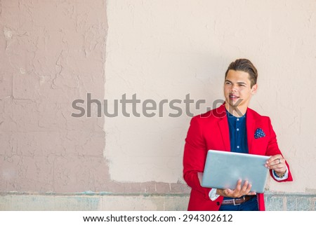 Businessman traveling, working in New York. Dressing in red blazer, blue collarless shirt, a young guy standing against wall on street, smiling, reading, working on laptop computer. Copy Space. - stock photo