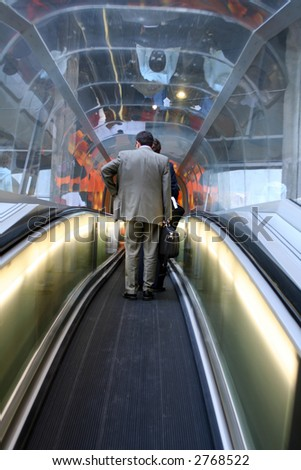 businessman travelling on airport escalator - stock photo