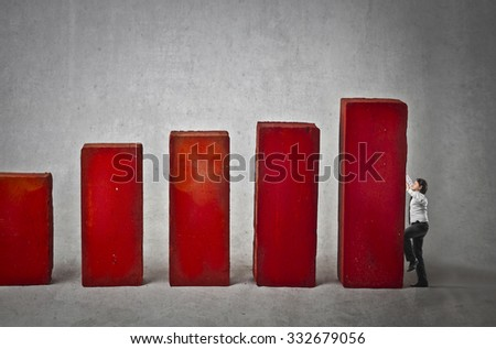 Businessman trying to climb on a column - stock photo