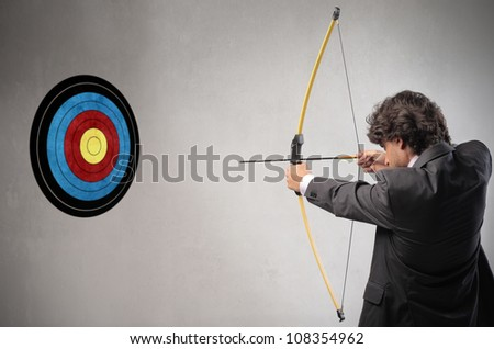Businessman trying to hit a target with bow and arrow - stock photo