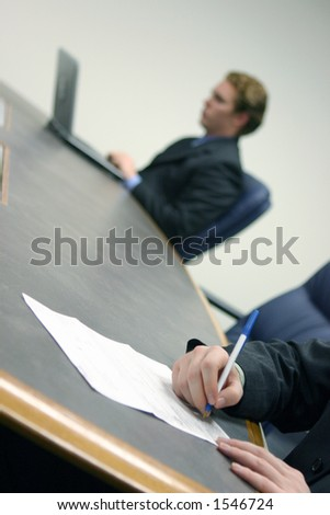 Businessman Types On His Laptop While Stock Photo Royalty Free - Conference table signs