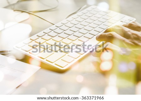 businessman typing on a keyboard at desk double exposure and blurred view of car on street at night - stock photo