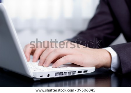 Businessman typing on a notebook (shallow DOF, hand in focus)