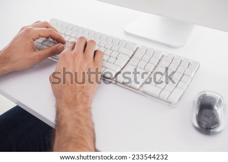 Businessman typing on computer keyboard in his office
