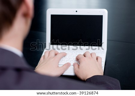 Businessman typing on his notebook. Above the shoulder view.