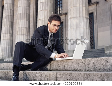 Businessman typing on laptop on stone stairs - stock photo