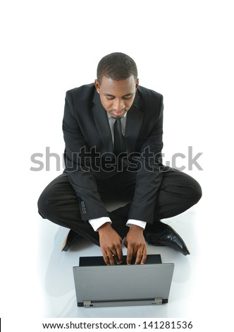 Businessman typing on laptop sitting on floor - stock photo