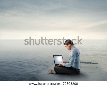Businessman un a wharf using a laptop - stock photo