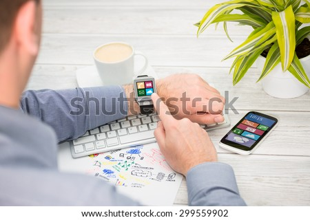 Businessman uses smart watch and phone. Smartwatch concept. - stock photo