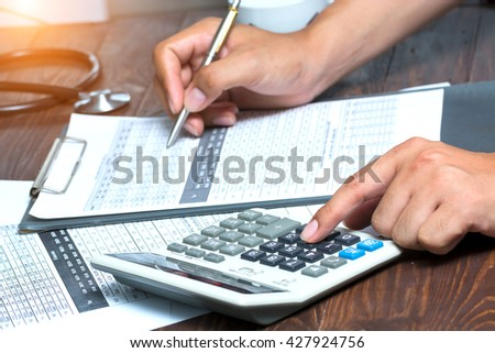 Businessman using a calculator to calculate the numbers - stock photo