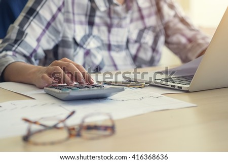 Businessman using a calculator to calculate the numbers in a office - stock photo