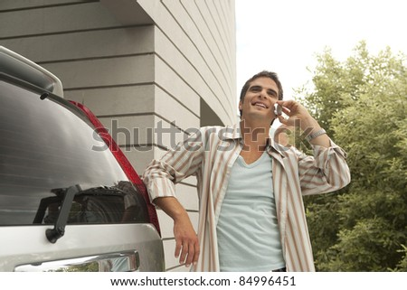 Businessman using a cell phone near a modern building, standing by his car. - stock photo